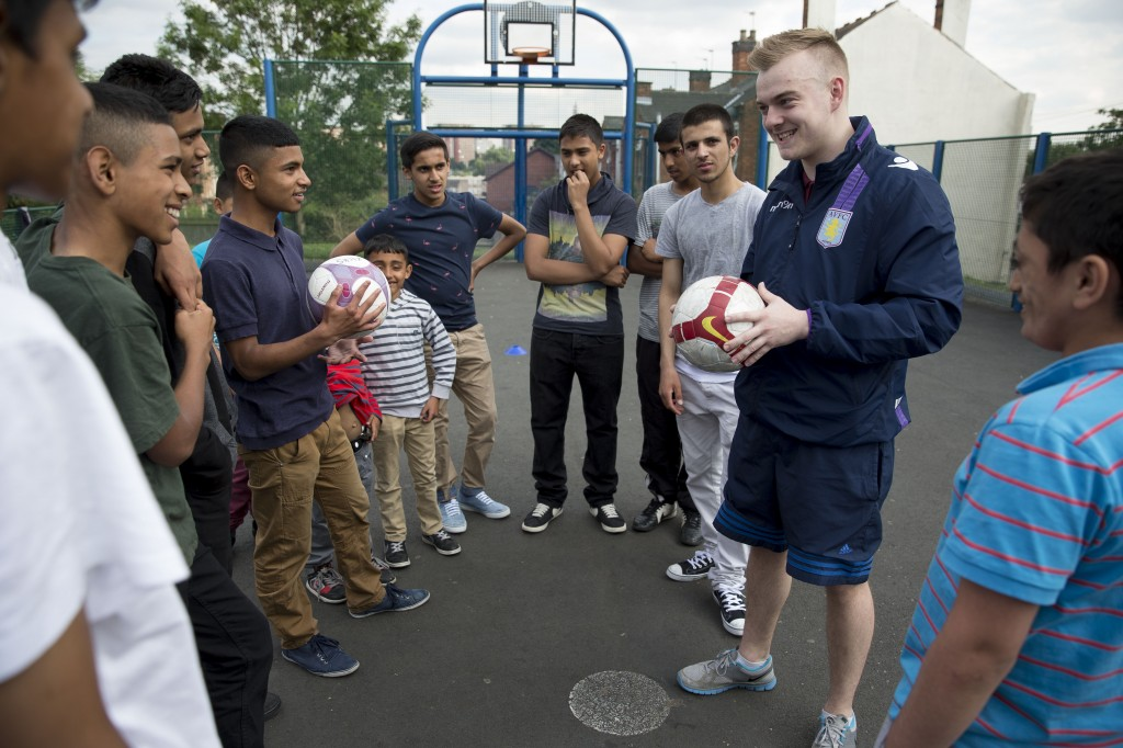 Photo showing Matthew Wilkes, Kicks coach with his enthusiastic participants.  Matthew started out as a Kicks' participant himself, graduating onto the Citizenship and Scholarship programme (delivered in partnership with Birmingham University), going full circle to become a Kicks coach.